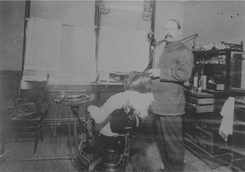 a black and white image of a man sitting in a dentist chair