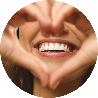 an image of a woman holding her hands in the shape of a heart in front of her smiling face