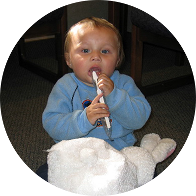 an image of a 6 month old baby playing with toys and putting them in his mouth